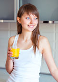 Young brunette girl with a glass of juice in the kitchen — Stock Photo