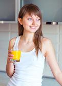 Jeune fille brune avec un verre de jus dans la cuisine — Photo