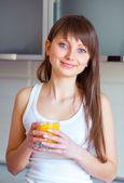 Mladá brunetka s sklenici šťávy v kuchyni — Stock fotografie