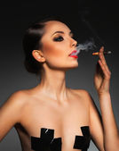 Portrait of a beautiful woman with cigar and with a glamorous re — Stock Photo