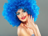 Portrait of a young beautiful girl with bright makeup in blue wi — Stock Photo