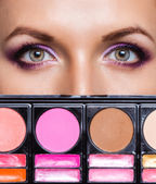 Closeup of beautiful eyes with makeup kit and glamorous makeup — Stock Photo