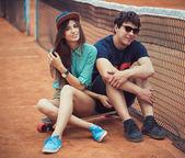 Jong koppel zittend op een skateboard op de tennisbaan — Stockfoto