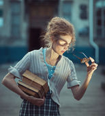 Funny girl student with books and glasses and a vintage dress — 图库照片
