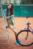 Beautiful young girl with longboard and bicycle standing on the  — Foto de Stock