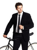 Attractive man in a classic suit with a bicycle on a white — Stock Photo