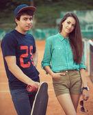 In piedi giovane coppia su uno skateboard sul campo da tennis — Foto Stock