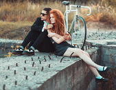 Guy with the girl and bicycle outdoors — Stock Photo