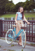 Young beautiful, elegantly dressed woman with bicycle — Stockfoto