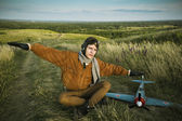 Guy in vintage clothes pilot with an airplane model outdoors — Stock Photo