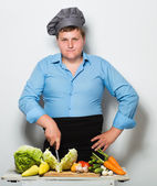 Plump cook on gray wall — Stock Photo