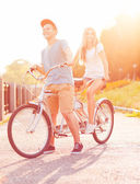 Happy couple riding a bicycle in the city street — Foto de Stock