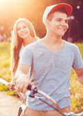 Happy couple riding a bicycle in the city street — Stock Photo