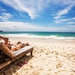 Relaxing and reading on the beach — Stockfoto