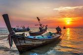 Loď nedaleko na pláži při západu slunce — Stock fotografie