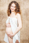 Happy pregnant woman in white shawl — Stock Photo