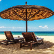 Wooden chairs and umbrellas on white sand beach — Stock Photo #45998459