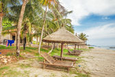 Wooden chairs and umbrellas on white sand beach — Stock Photo