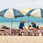 Beach masseuses resting under umbrellas — Stock Photo #48697327