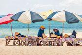 Strand masseurinnen ruhelosigkeit unter sonnenschirmen — Stockfoto