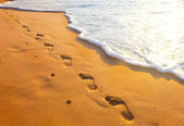 Footsteps of one-legged people at sunset time — Stock Photo