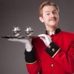Улыбаясь официант в красной форме — Стоковое фото