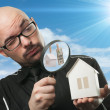 Stock Photo: Man with a magnifying glass and paper house