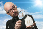Man with a magnifying glass and paper house — Stock Photo
