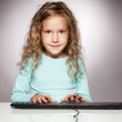 Little girl with computer keyboard — Stock Photo