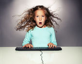 Surprised a girl with computer keyboard — Stock Photo
