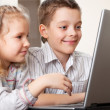 Royalty-Free Stock Photo: Happy kids playing laptop at home