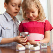 Children are considering magnifying glass collection of stones — Zdjęcie stockowe #12359531