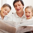 Family reading a newspaper — Stock Photo #12359734