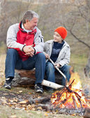 Grandfather and grandson around a campfire — Stockfoto