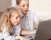Surprised child with laptop indoors — Stock Photo