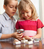 Children are considering a magnifying glass collection of stones — 图库照片