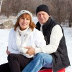 Mature couple sledding — Stock Photo