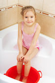 Girl holding his feet in cold water. Harden — Stock Photo