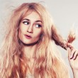 Young woman looking at split ends - Stockfoto