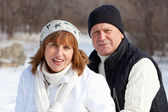 Happy seniors couple in winter park — Stock Photo