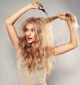 Young woman looking at split ends — Stock Photo