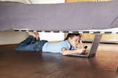 Child with laptop and phone under the bed — Stock Photo