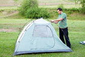 A man puts a tent — Stock Photo