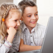 Happy kids playing laptop at home — Stock Photo