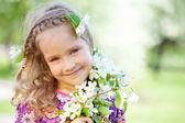 Little girl with branches blossoming apple tree — Stock Photo