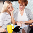 Mother and daughter read magazine at home — Stock Photo #24713763