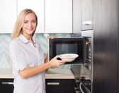 Woman warms up food in the microwave — Stock Photo