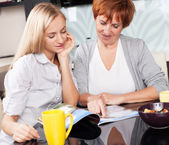 Mother and daughter read magazine at home — Stock Photo