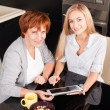 Mother and daughter looking in tablet pc — Stock Photo