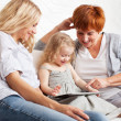 Family wiht tablet computer at sofa — Stock Photo #25128877